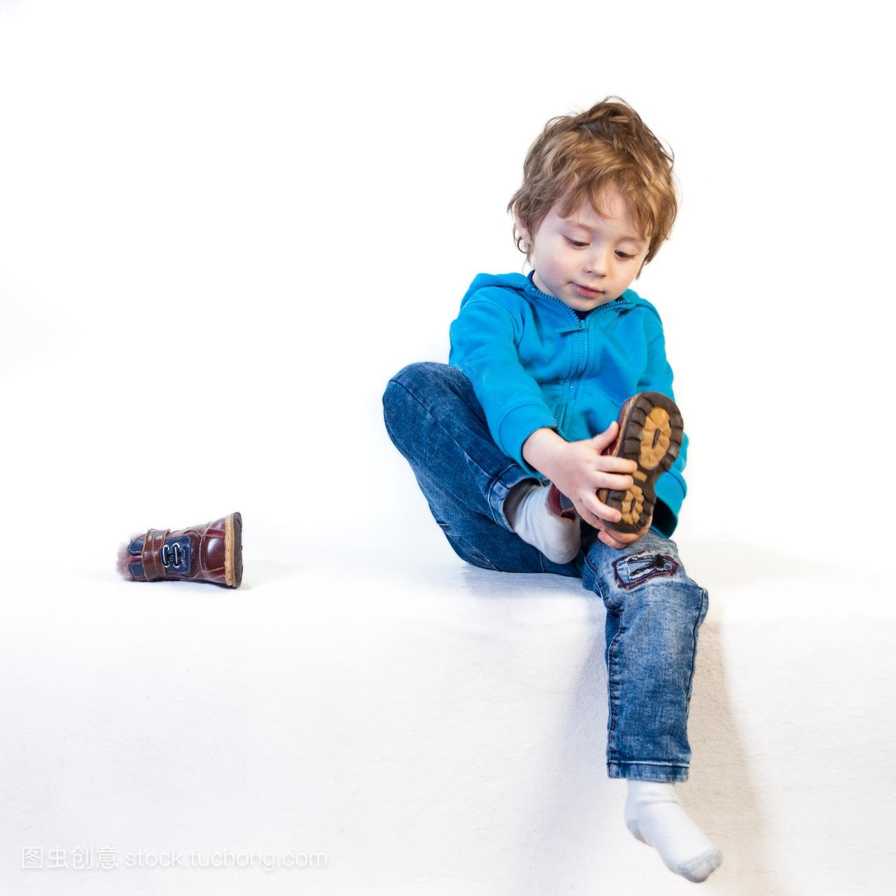 一个三岁的小孩试着穿鞋。隔离在一个图解枪喷火图片