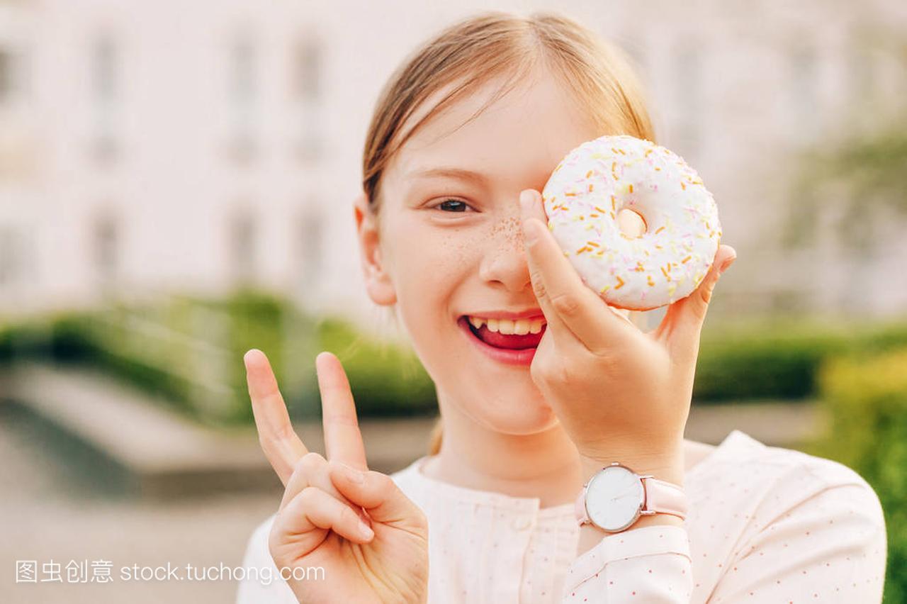 肖像滑稽小女孩的特写玩甜甜圈,戴着手表,用手qq飞车裙子女生图片