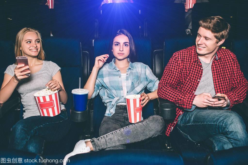 非常好的年轻金发坐在一起在电影院里。女生女像长的得朋友男明星图片