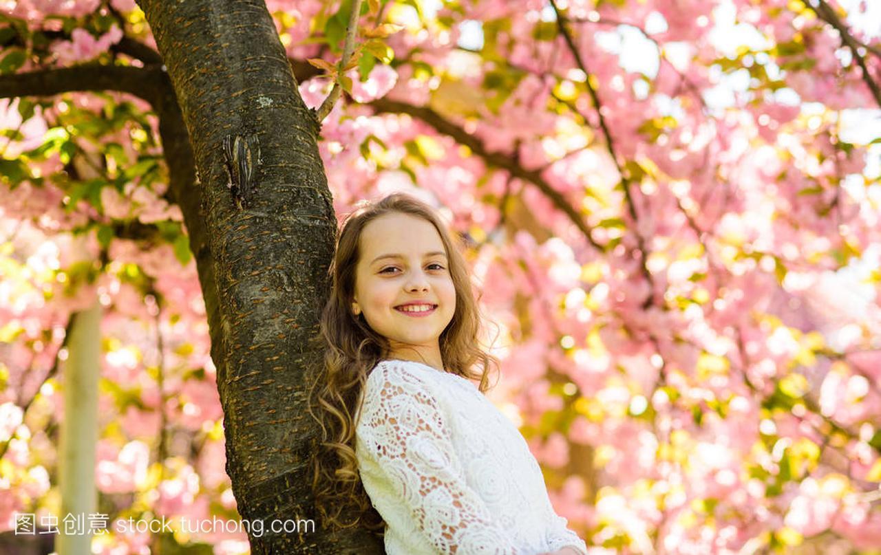 女生在v女生的树干依靠在樱花附近,站立女孩。长发发型面孔欧美图片