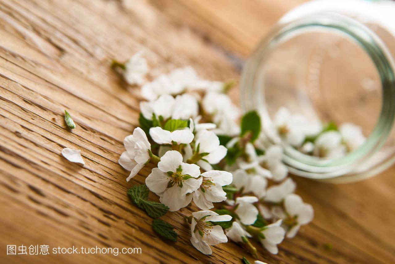 花束木桌上的女生春天花和透明白色的罐子学生头头像背景图片