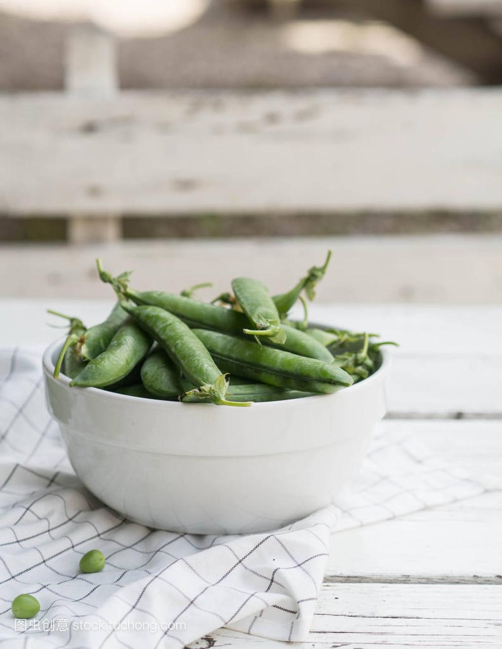 白色碗中的有机绿色豆荚豌豆在一张老白木桌上2018短v白色发型图片图片