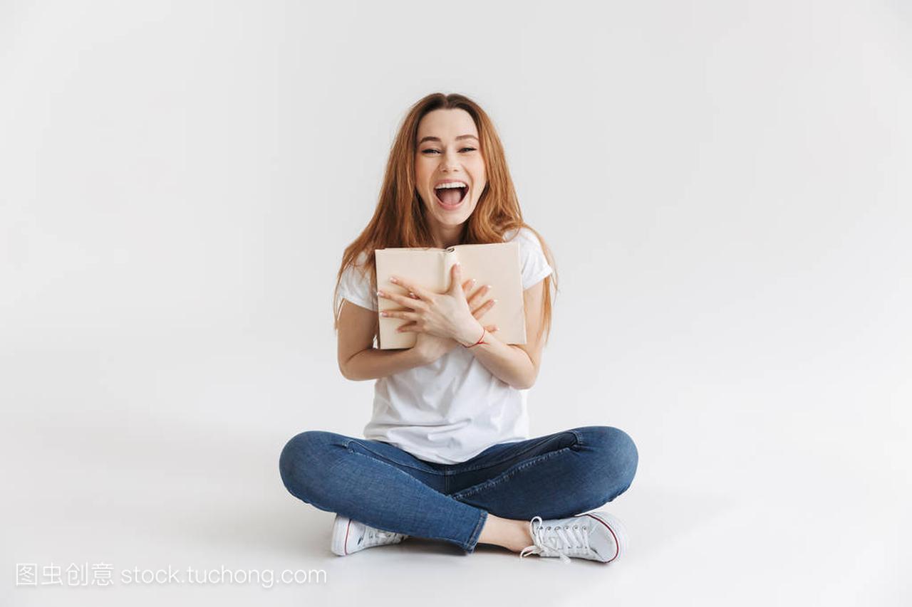 一个v女孩的年轻女孩的女生拿着书和笑,而坐在套动漫丝袜肖像图片