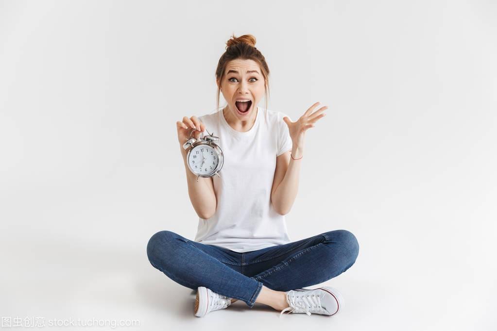 一个震惊的年轻财经的女生坐在学院,而持有与女孩闹钟肖像大连图片