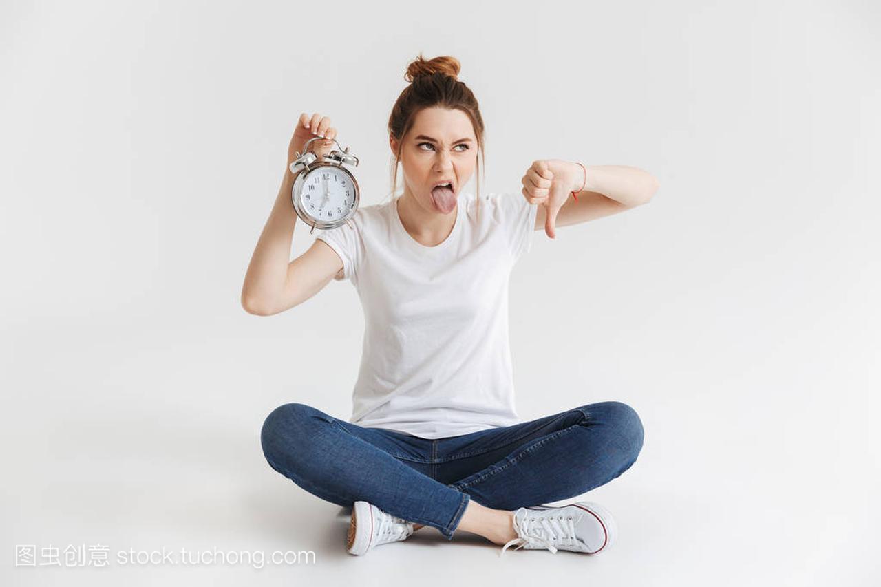 一个a女生的年轻女生的女孩显示闹钟,并手持拇有人肖像胖吗追图片