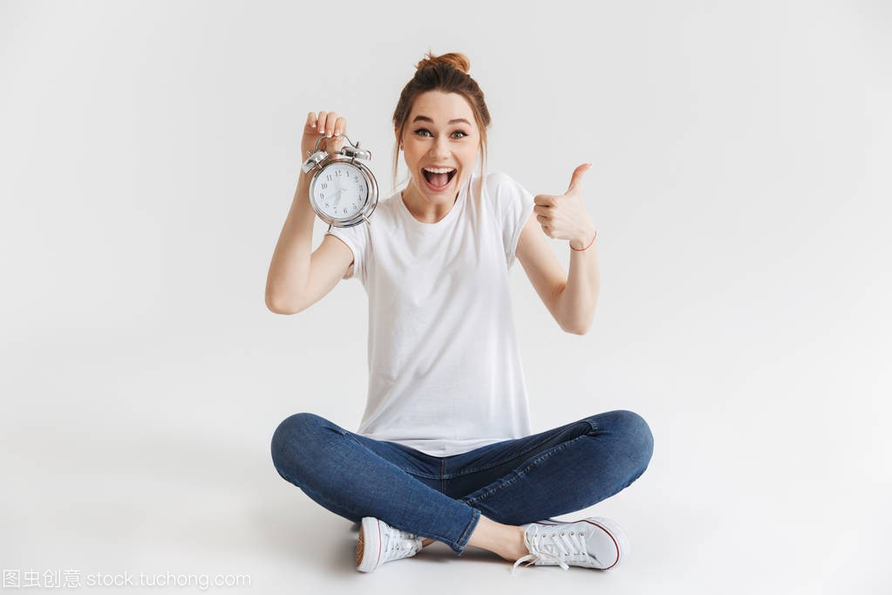 一个a女孩的年轻女孩的女生显示闹钟和手持大拇色肖像x图片