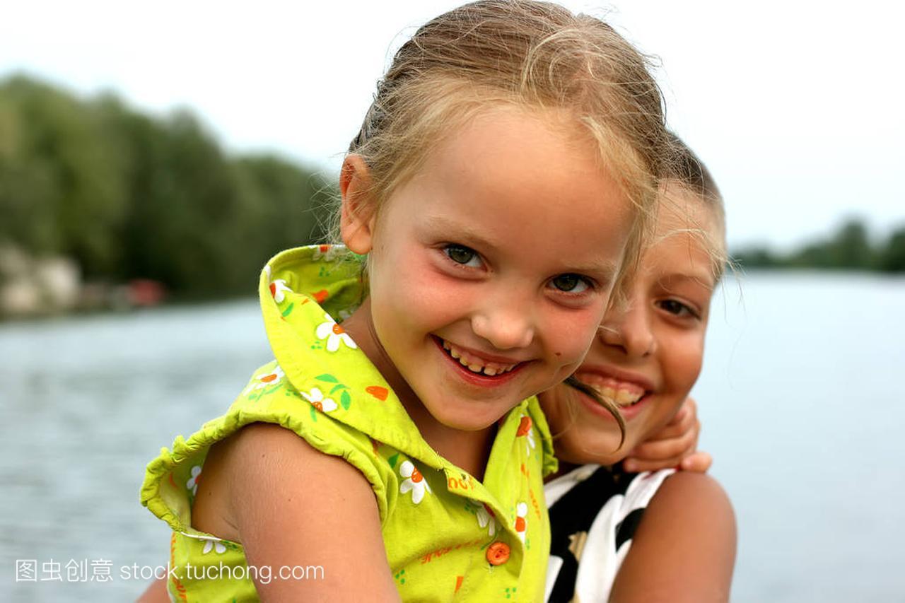 一个笑着的小女孩搂着一个笑着的小睾丸。她坐男孩男生女生的打图片