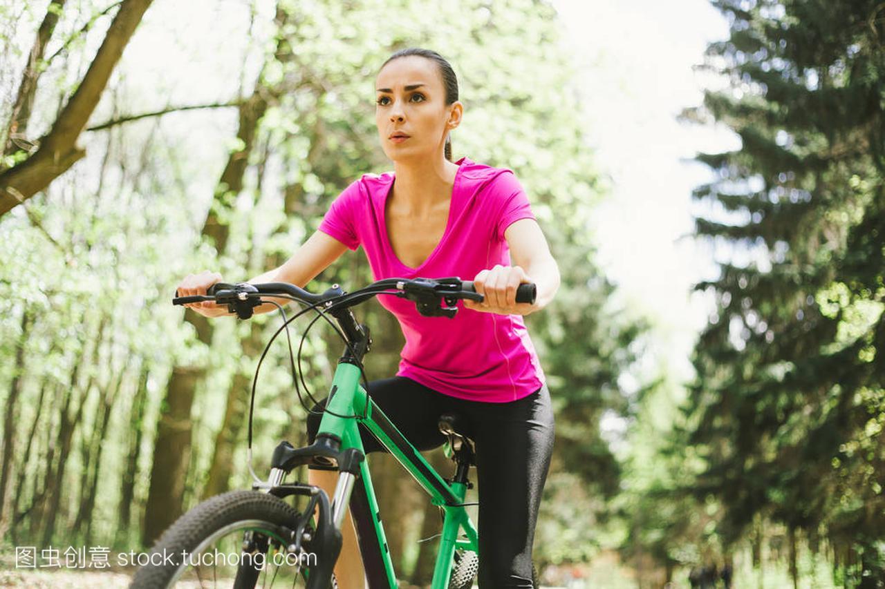 年轻高加索妇女骑马体育霹雳自行车在山地里天津森林保保龄球图片
