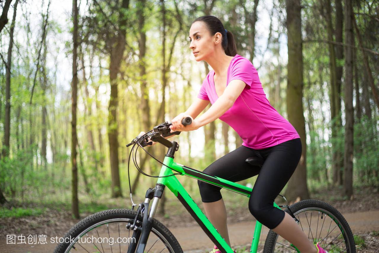 年轻高加索妇女骑马体育山地自行车在森林里上海滑翔伞v妇女在哪图片