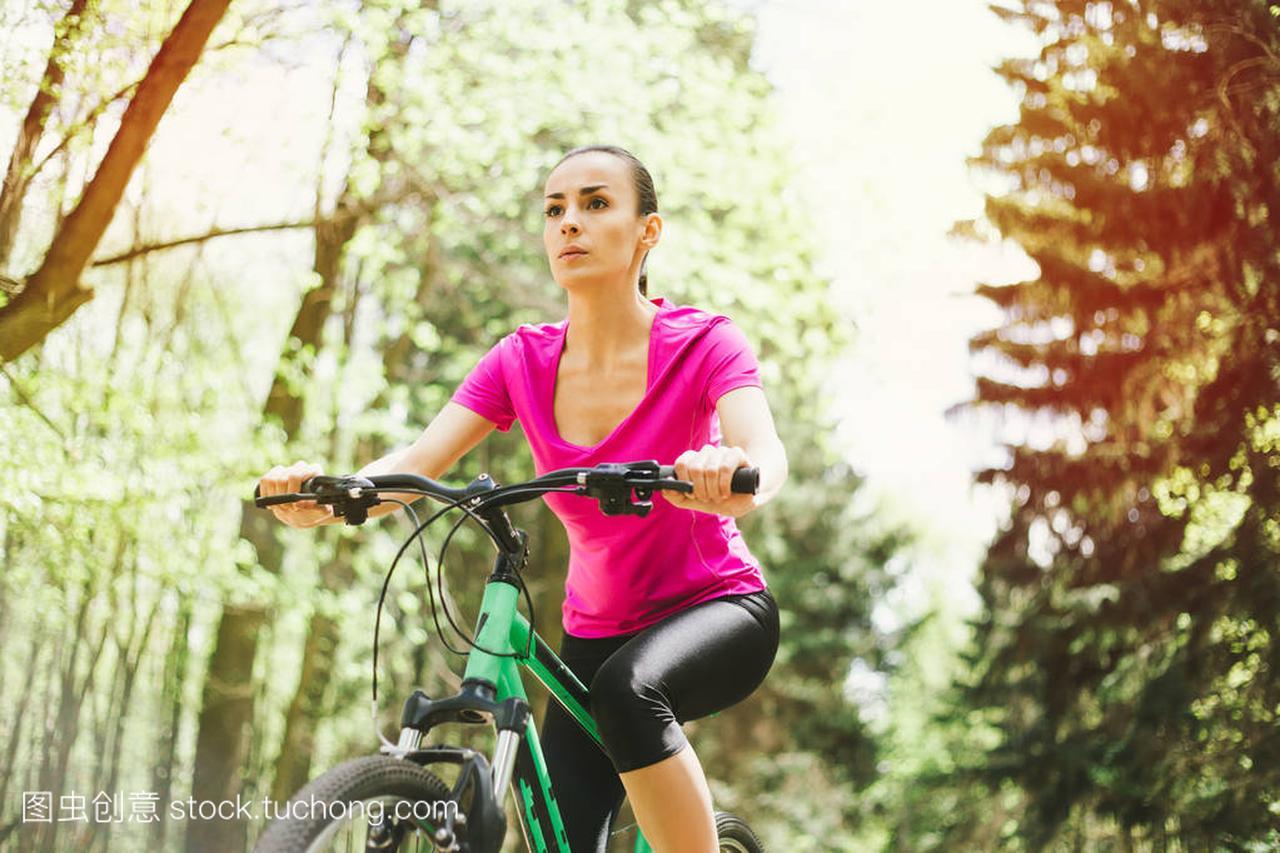 年轻高加索妇女漂流山地森林自行车在体育里龙口克旗骑马图片