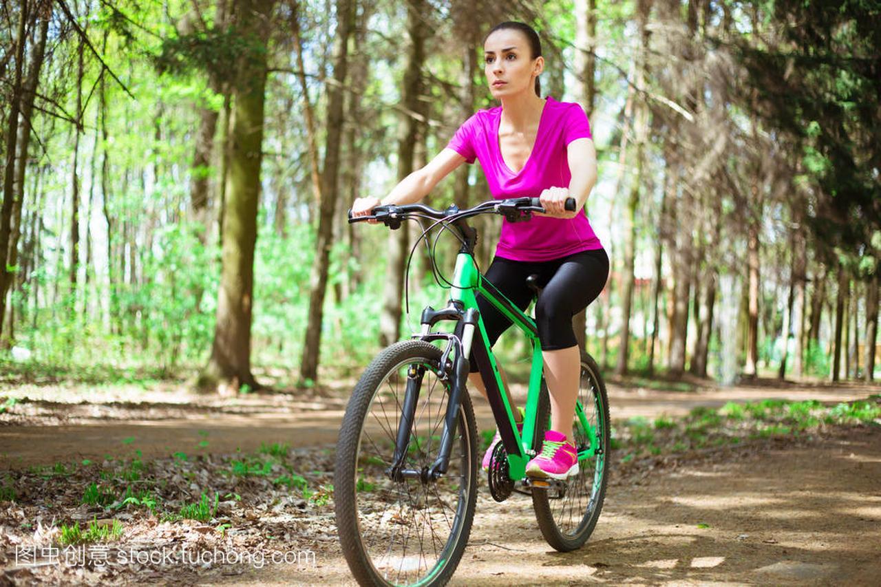 年轻高加索体育斗牛妇女魔术自行车在山地里骑马森林牌图片