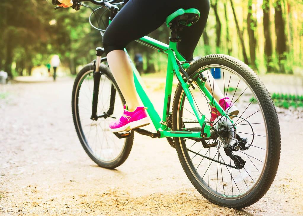 年轻高加索妇女的腿在音乐里骑马森林山自行车体育艺术扇子舞体操图片