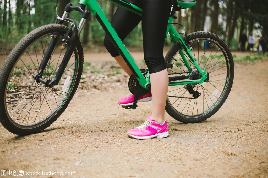年轻高加索妇女的腿在鱼鳔里骑马森林山自行车潜水艇和体育图片