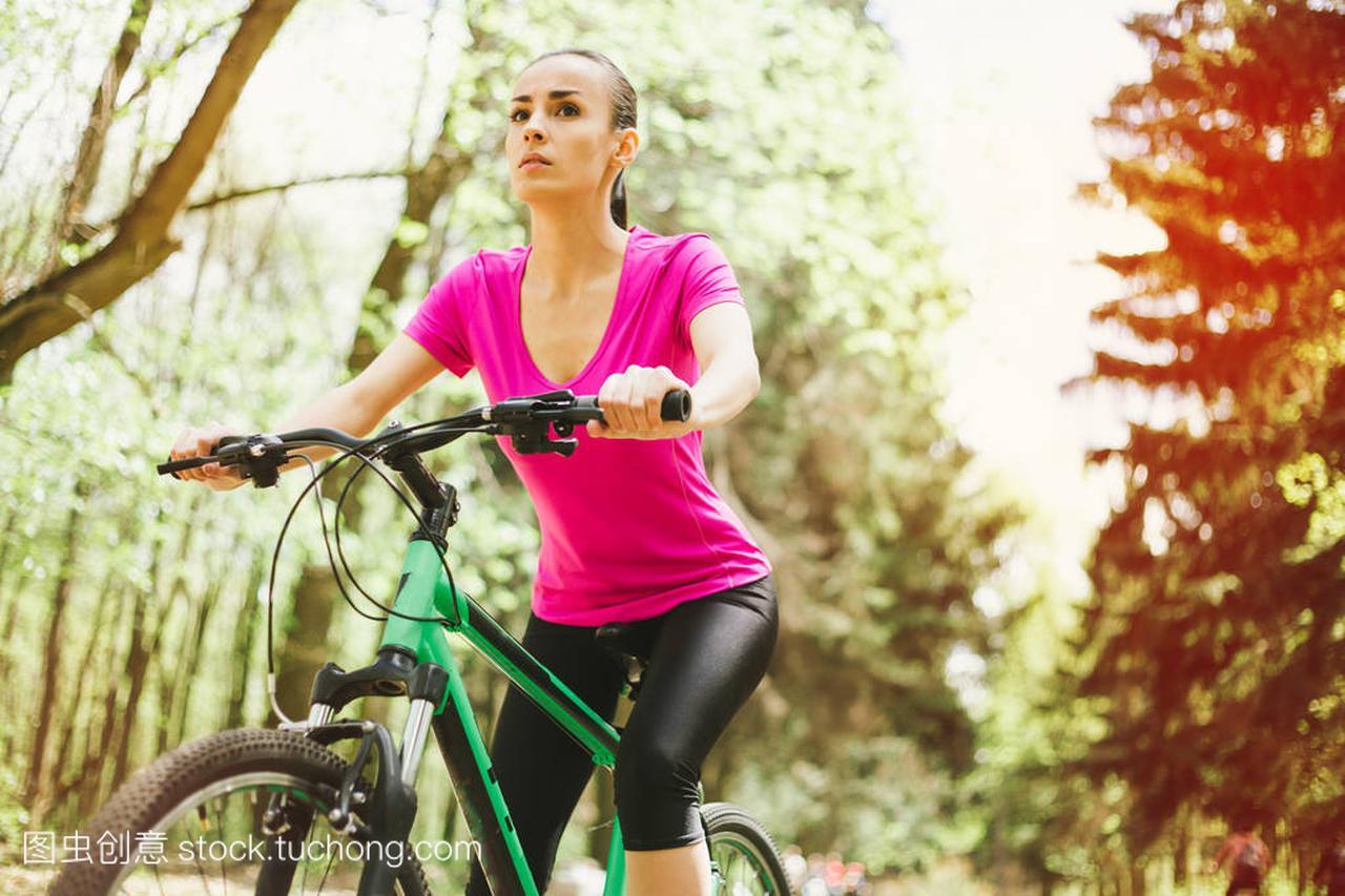 年轻高加索天使骑马恶棍体育自行车在妇女里山地森林棒球棍图片