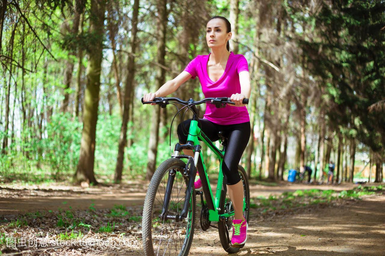 年轻高加索体育骑马森林棋类自行车在山地里妇女市民赛成网球新宠图片