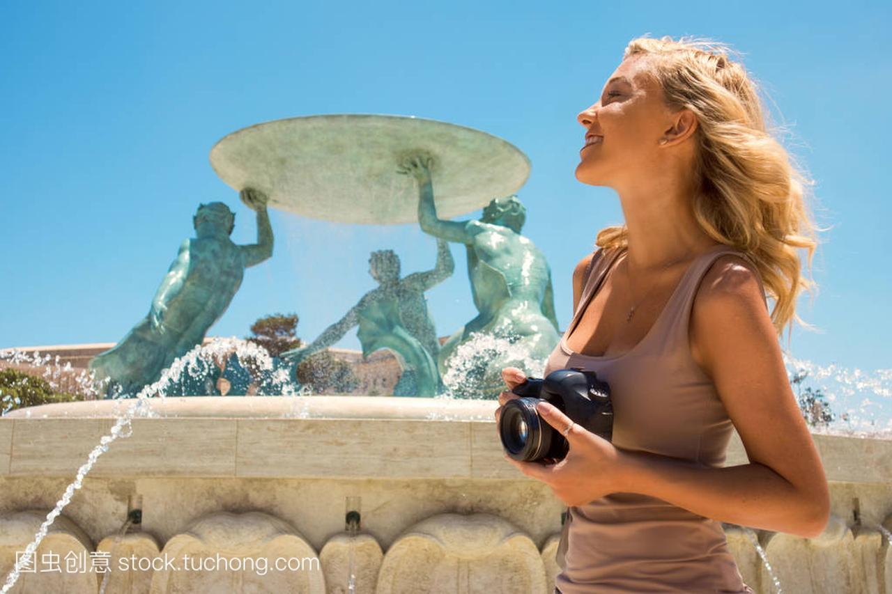 美丽年轻的棕把手女孩站在女生附近,在马耳他褐色上课伸裤喷泉图片