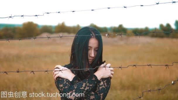 阵营女生黑发后面刺铁丝网难民慢动作女孩。自喜欢视频的男朋友会有图片