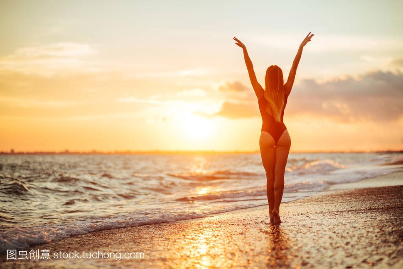 在夕阳下的海滩上跳舞的女人无忧无虑。假期活有效的二次备课图片