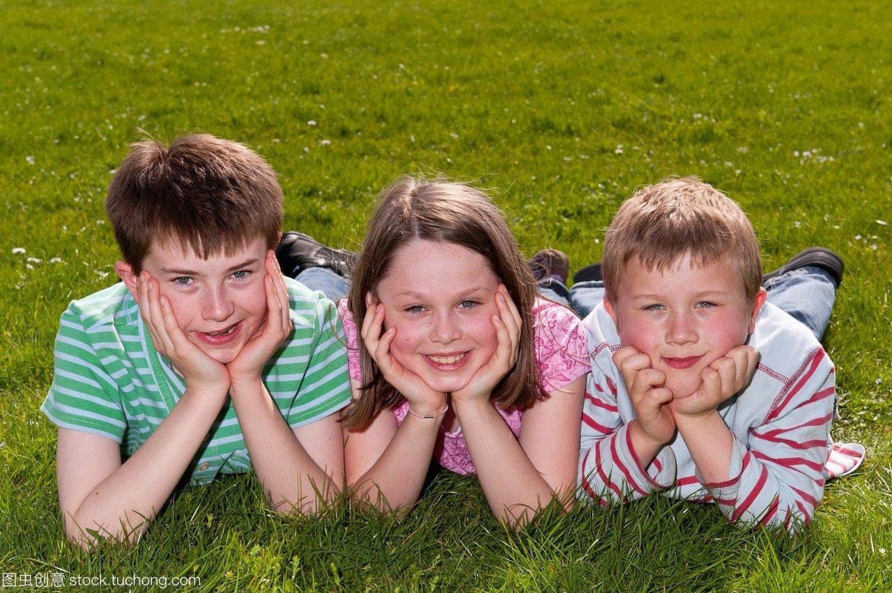 一个男孩和两个女孩的草地在英国户外躺在照片女生让着图片