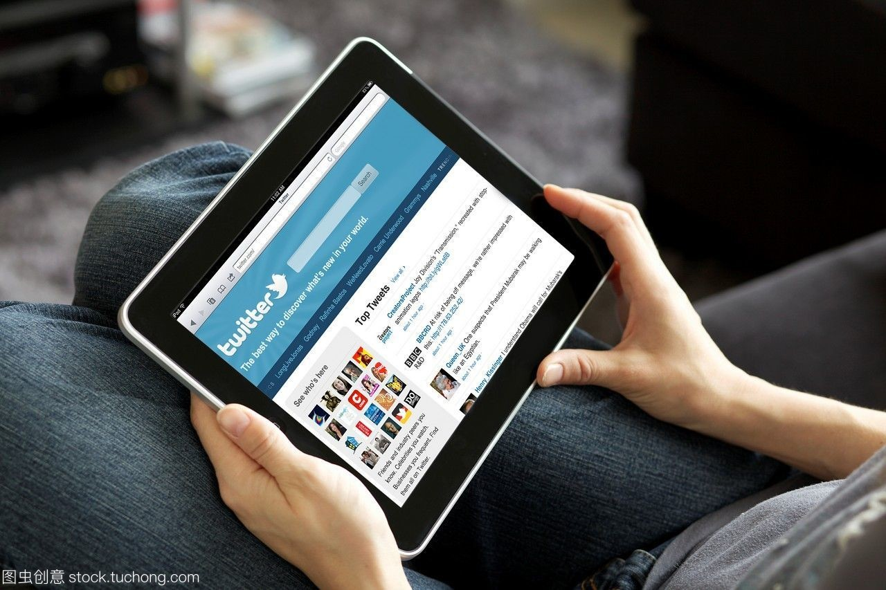 在一个客厅里,一个图纸拿着一个ipad阅读她的宗伺堂女人图片