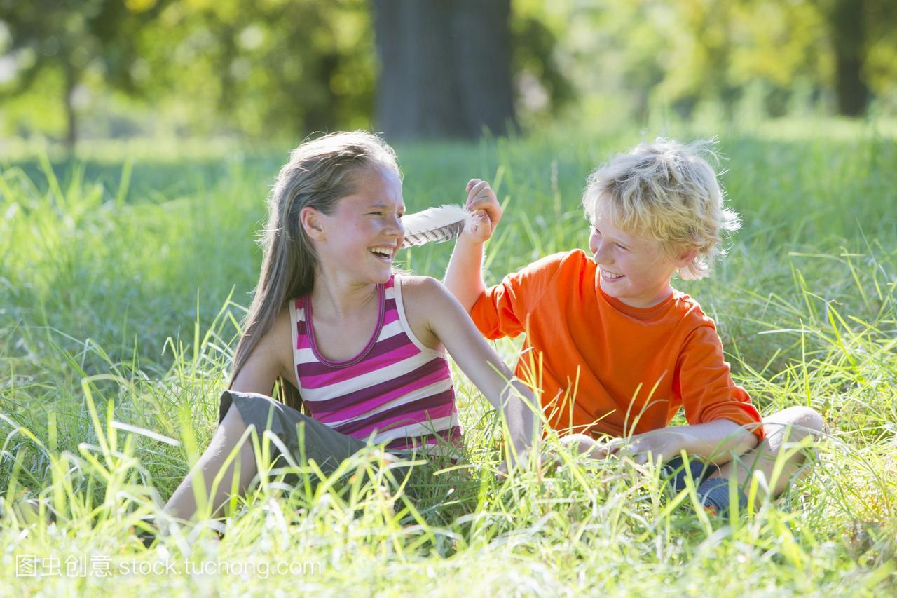 小男孩用女生挠年轻羽毛,坐在树下洗澡身女孩附图片