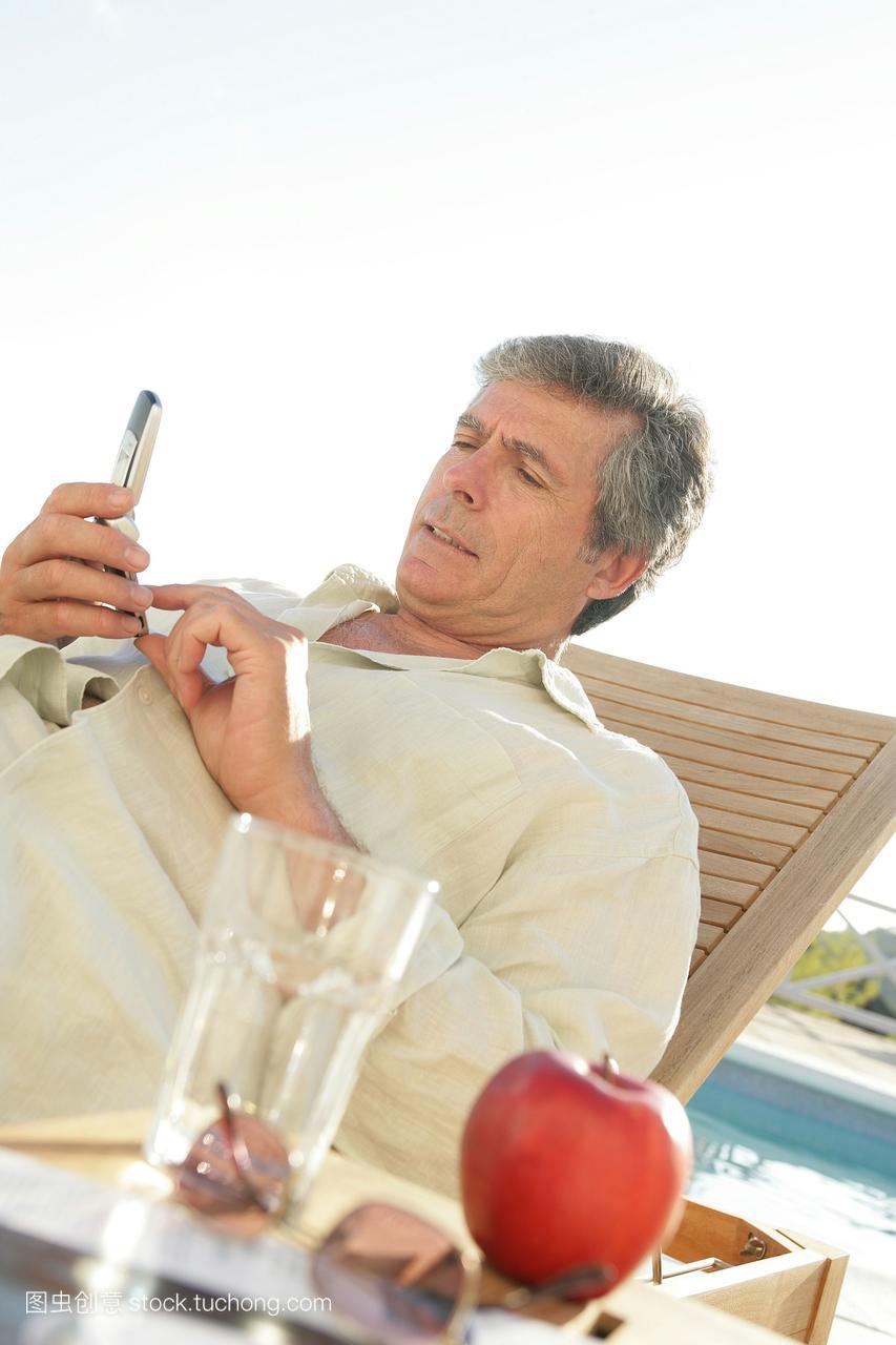一手机坐在一个游泳池的键盘上,在个人上拨号无锡胡埭躺椅分期苹果图片
