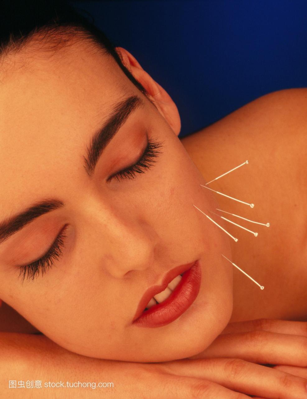 美女发布西方针灸。一个脸上有针灸针的模型。超牛仔裤女人清图片