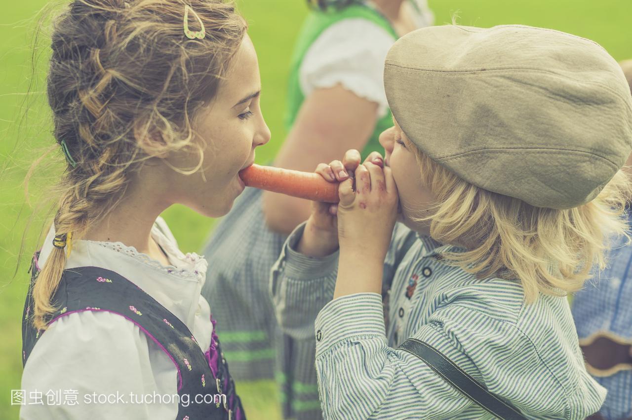 德国,萨克森,女孩和男孩一起咬掉胡萝卜中学女生包养图片