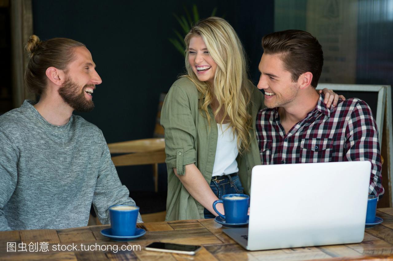 快乐的年轻男女朋友在咖啡厅交谈