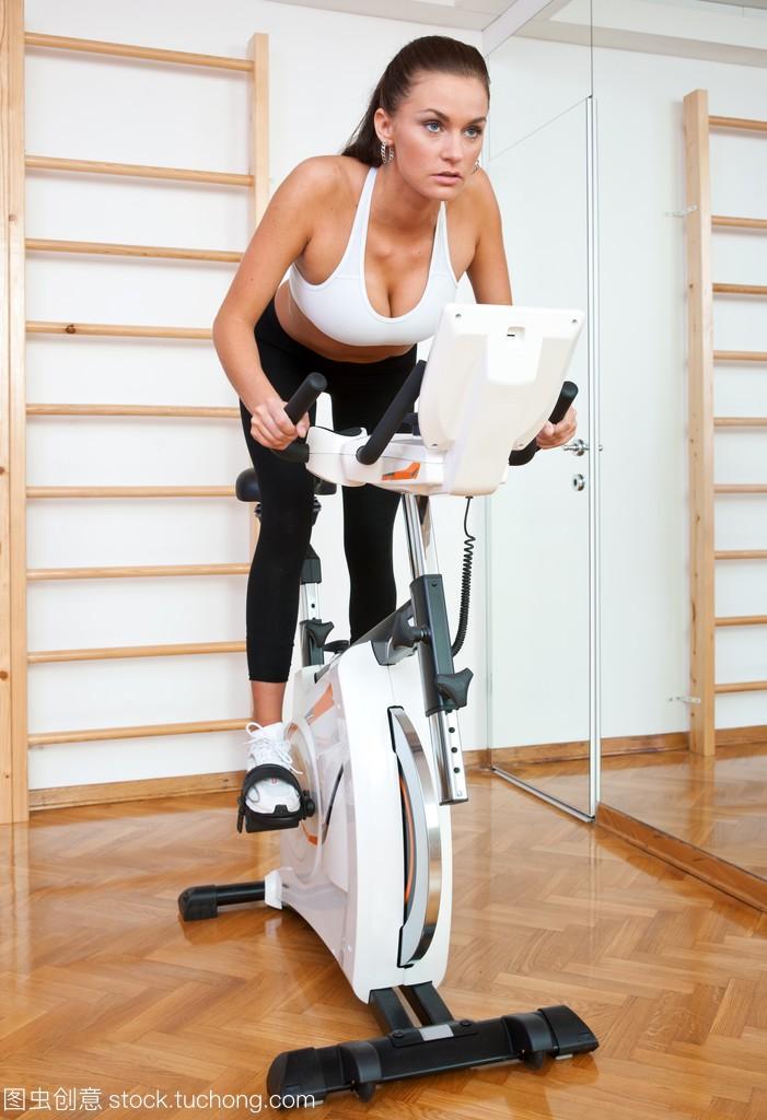 在健身房的固定式自行车上适合的女人