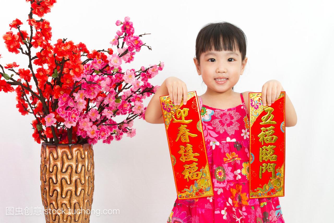 hinese little girl pising holding Spring festival couplets