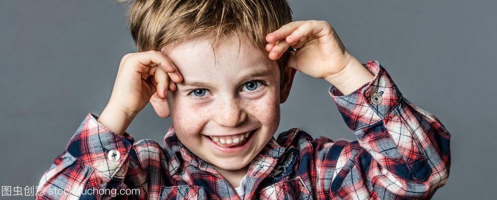 厚脸皮男学龄前儿童有雀斑玩着他的手