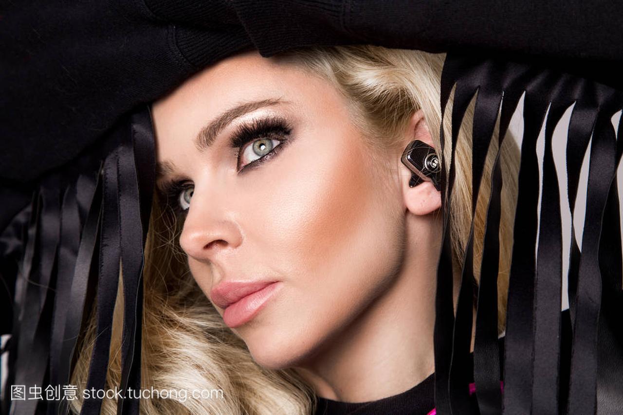 美丽性感金发女郎,有着完美的脸,并在耳耳机听