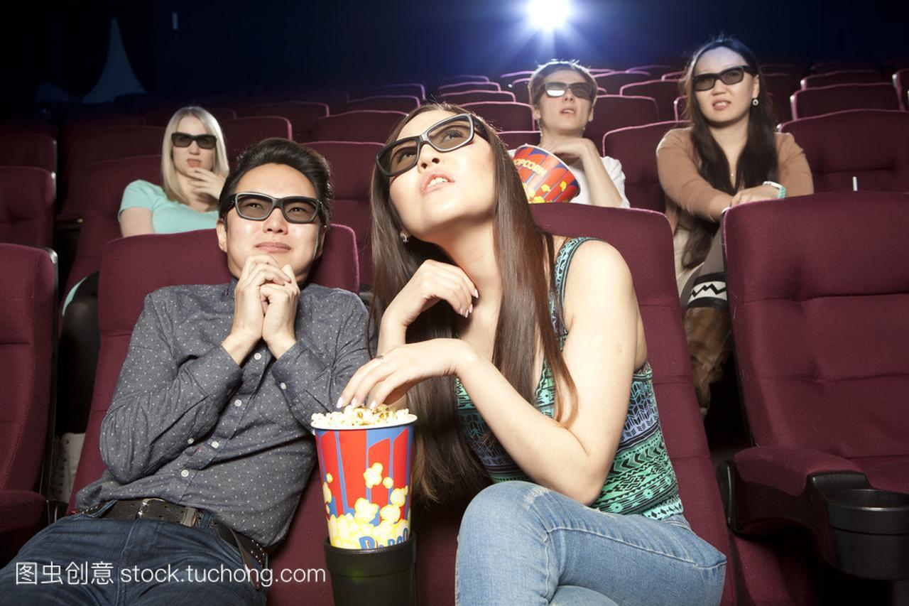 对年轻情侣坐在电影院里戴着 3d 眼镜看