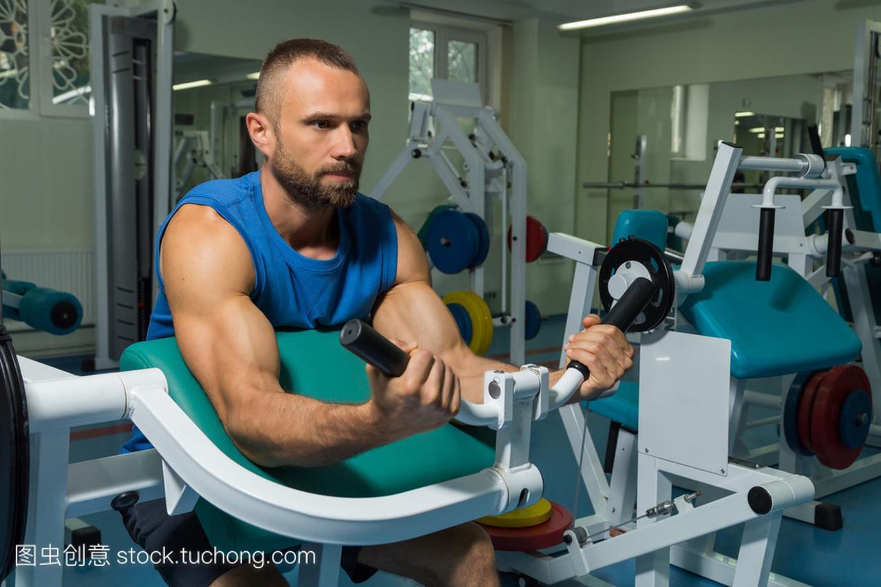 运动员板凳在健身房在模拟器上的二头肌。在模