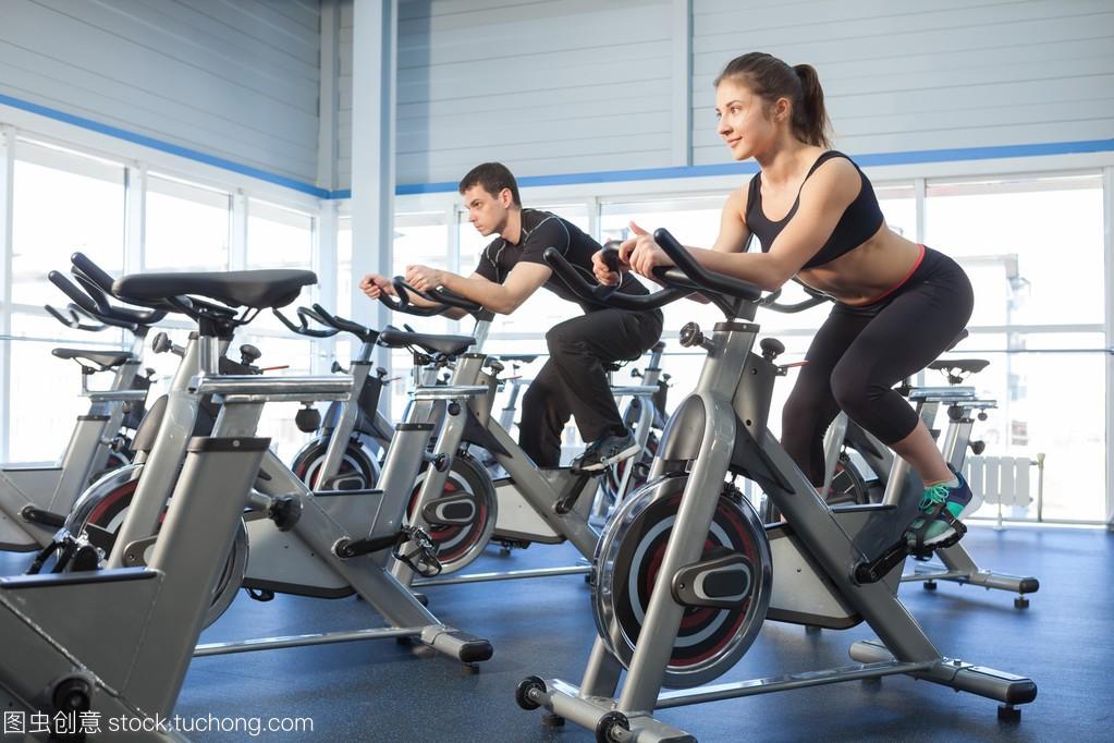 男人和女人锻炼在健身房里的自行车