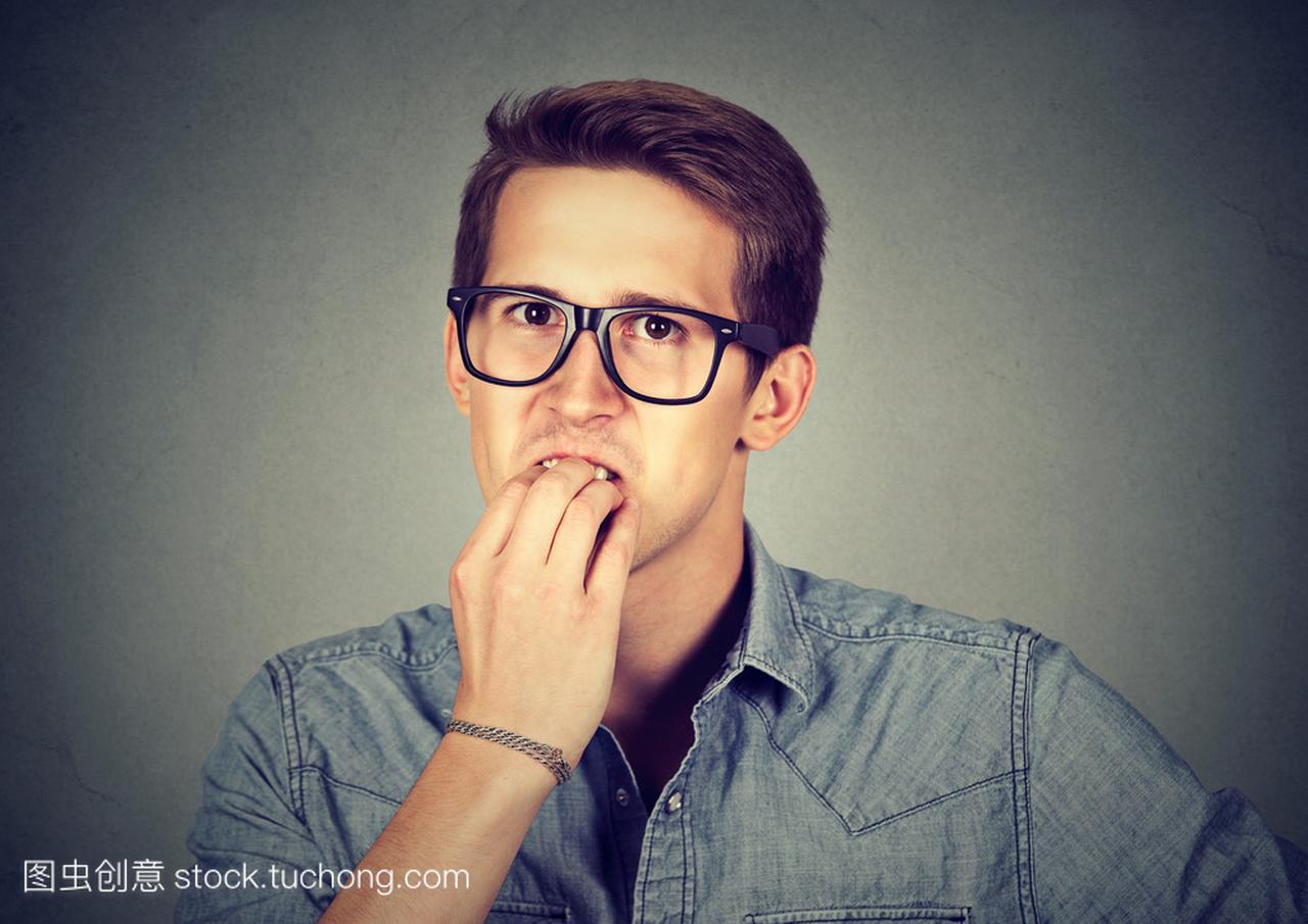 Preoccupied anxious man biting fingernails nervously