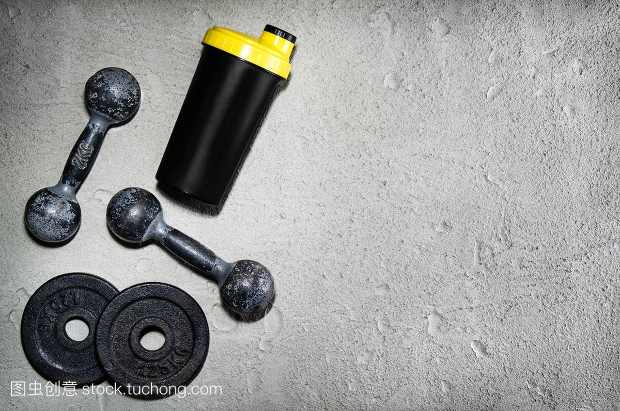 健身或健美的背景。老铁哑铃在健身房里的混凝