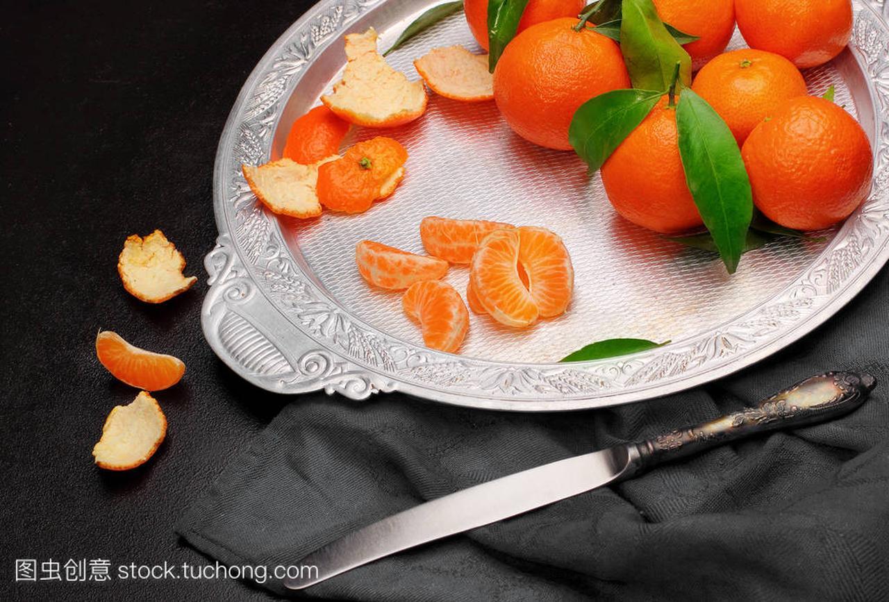 新鲜橘克莱门泰因与叶在银托盘 knifeon 暗石背