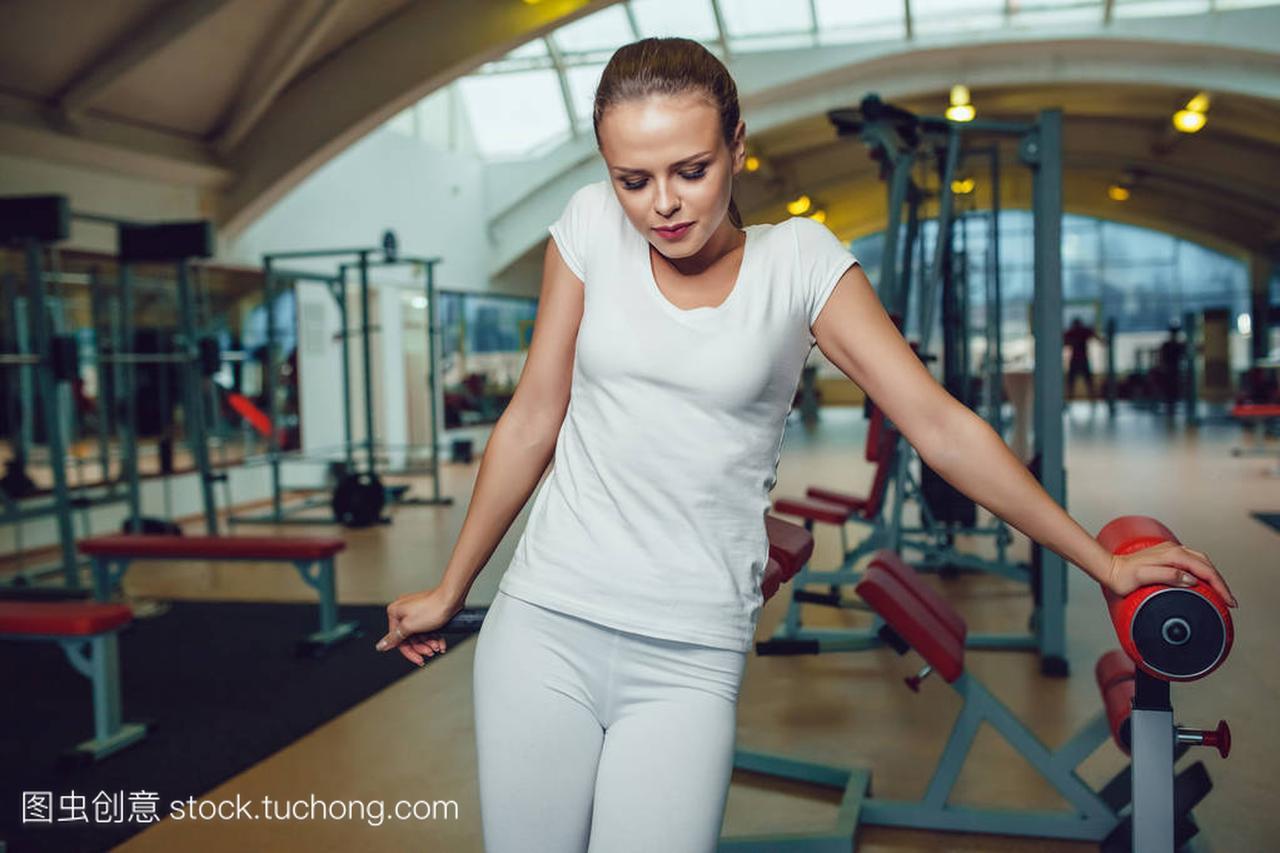 漂亮的女孩站在健身房里穿空白的白色 t 恤和紧
