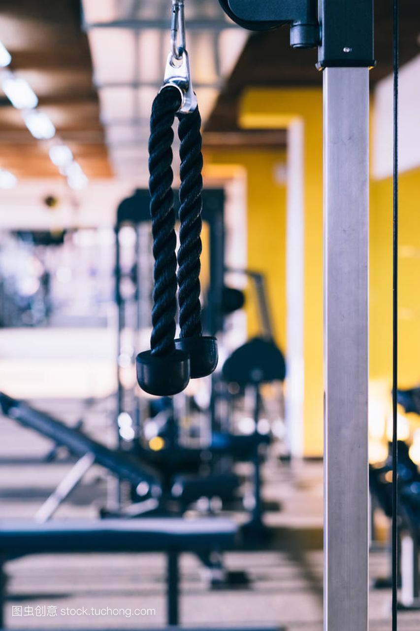 健身馆,很多机器,绳子在下拉详细
