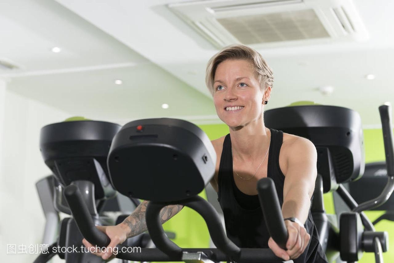 微笑在健身房健身脚踏车上合适的年轻女人