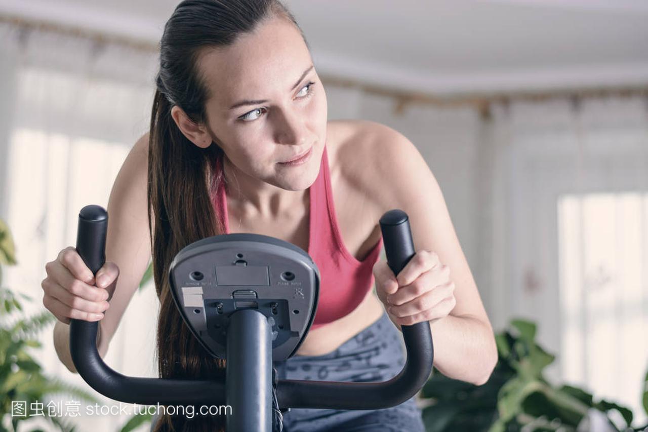欧洲妇女训练有氧健身运动在家里锻炼自行车。