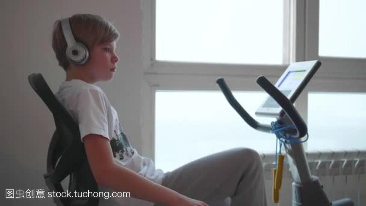 少年在耳机听音乐在一个固定的自行车健身。健