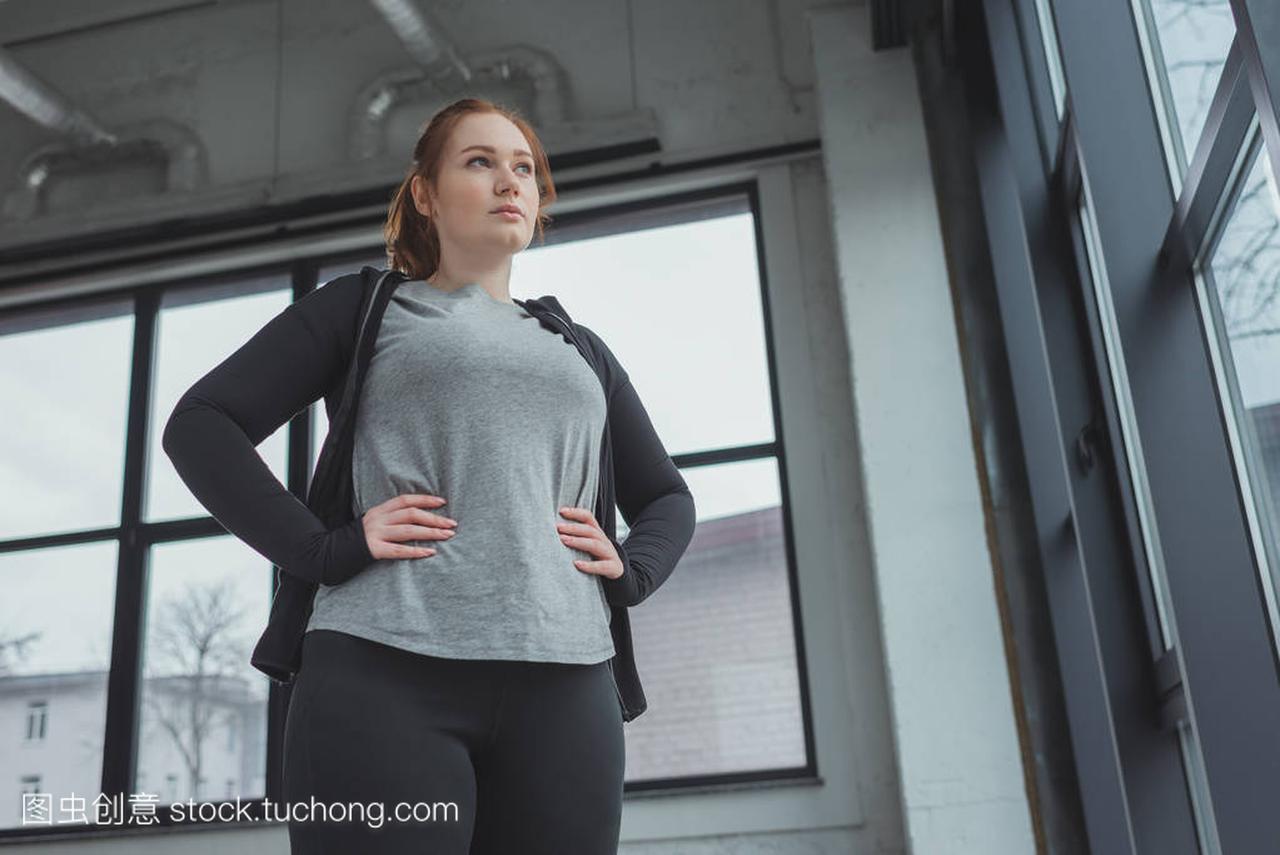 穿运动服的超重女孩在健身房靠窗站立