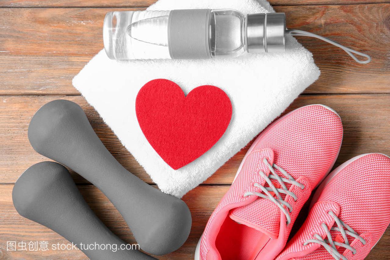 健身房的东西和红色的心在木质背景。心肺训练