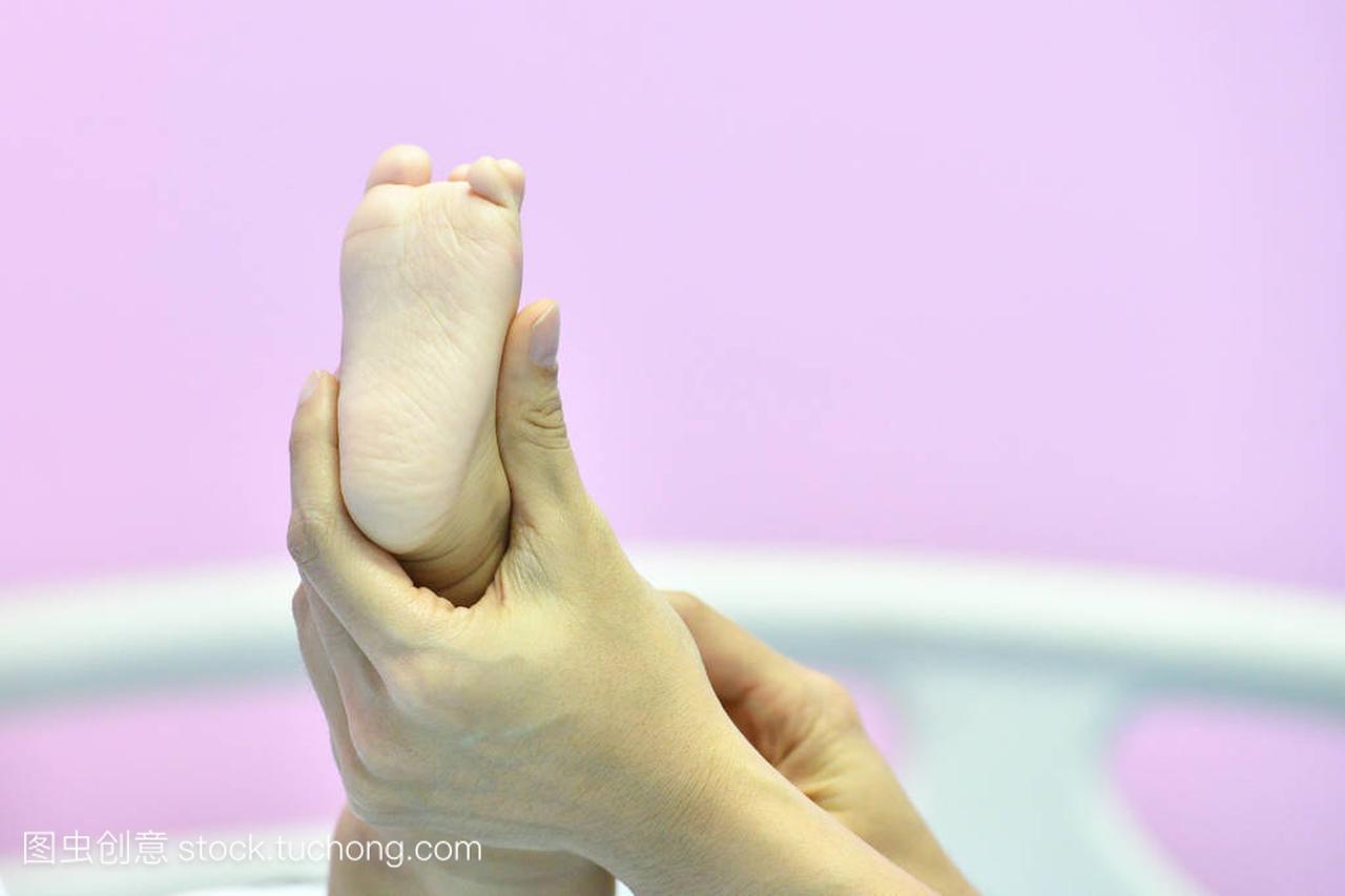 医生抱着小婴儿的脚在医院里