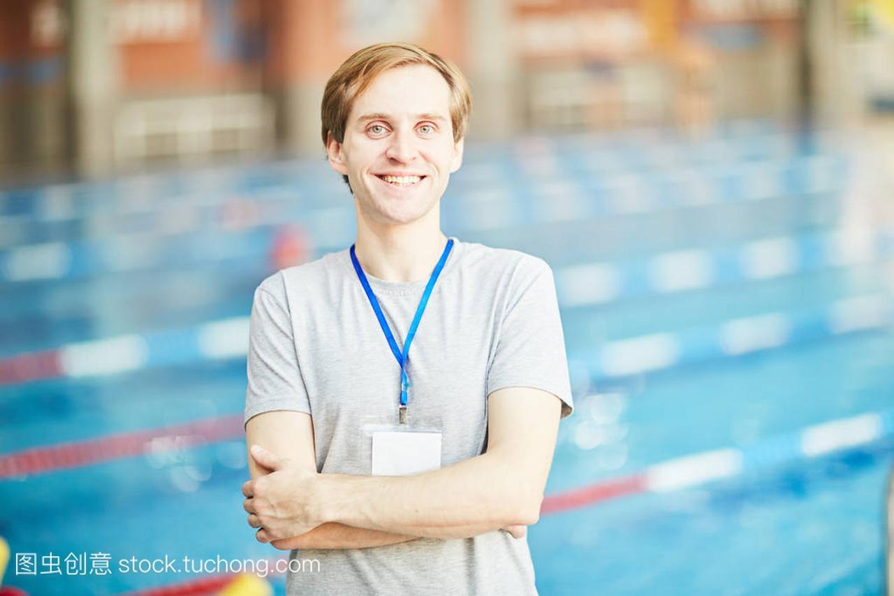 快乐成功的教练游泳与徽章挂在他的脖子上, 交