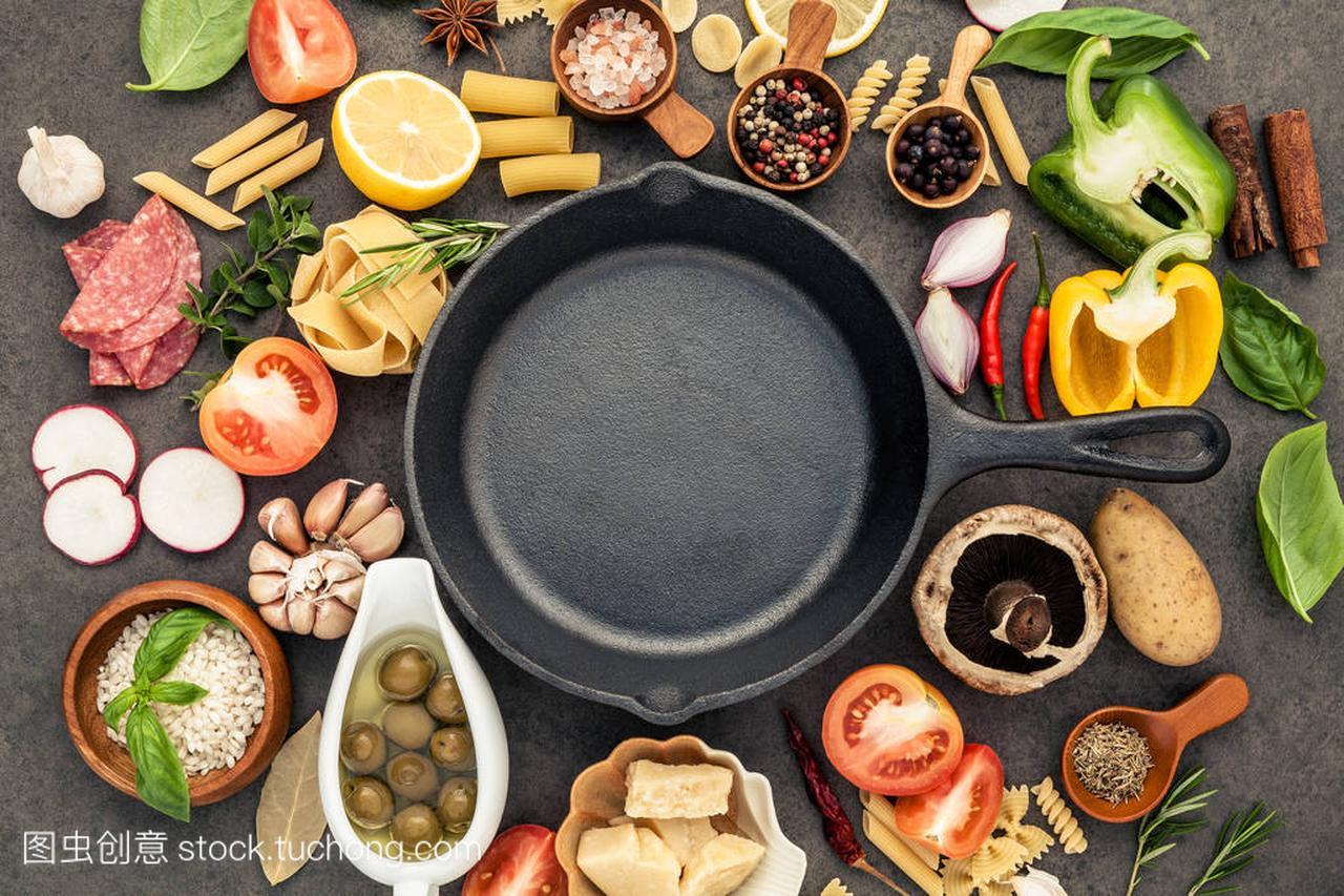 意大利食品烹饪原料上暗石背景与铸铁潘平躺和