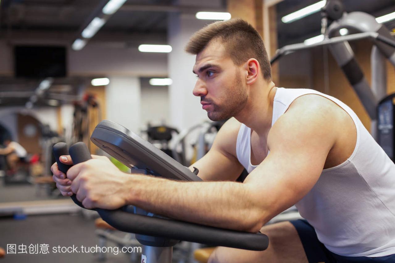 健身男子在自行车做纺纱在健身房。适合年轻男